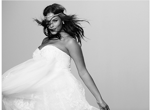 Curvy model dancing in strapless bridal dress