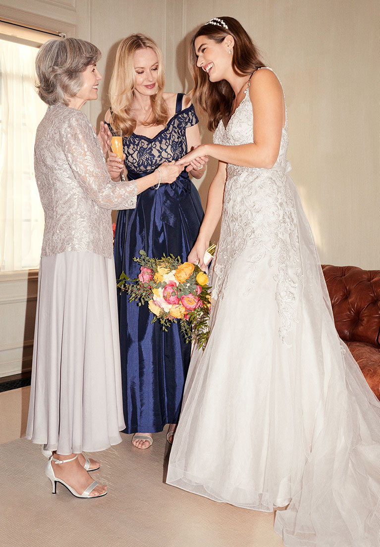 Bride standing with mom and grandmother showing off her ring