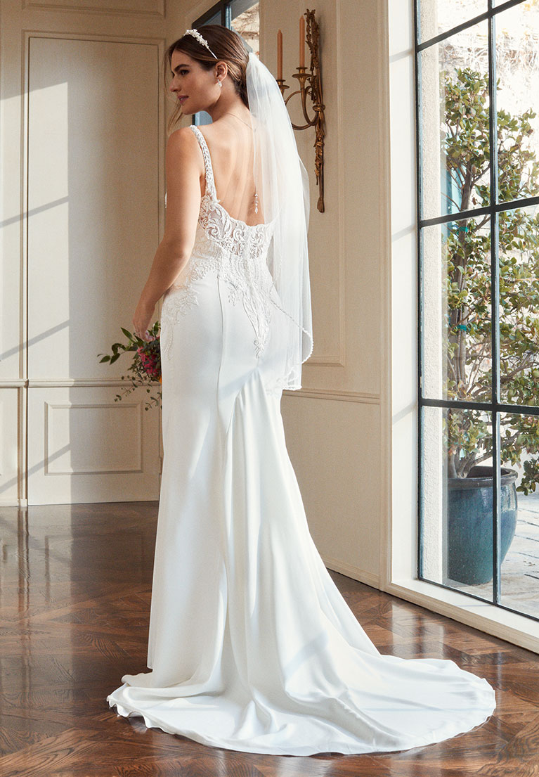 Bride standing with her back to the camera next to large window