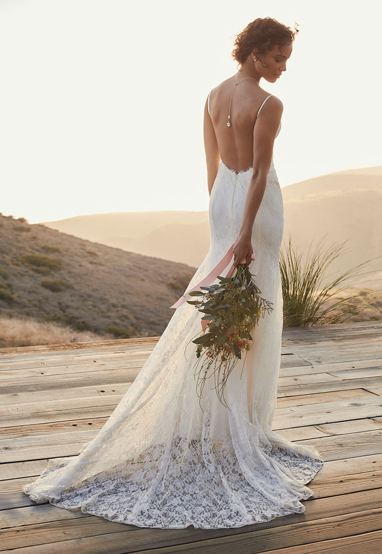 Bride standing on seaside deck draping bouquet behind her