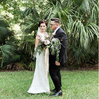 Bride and groom standing in front of greenery