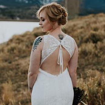 Bride with tattoos showing her backless dress