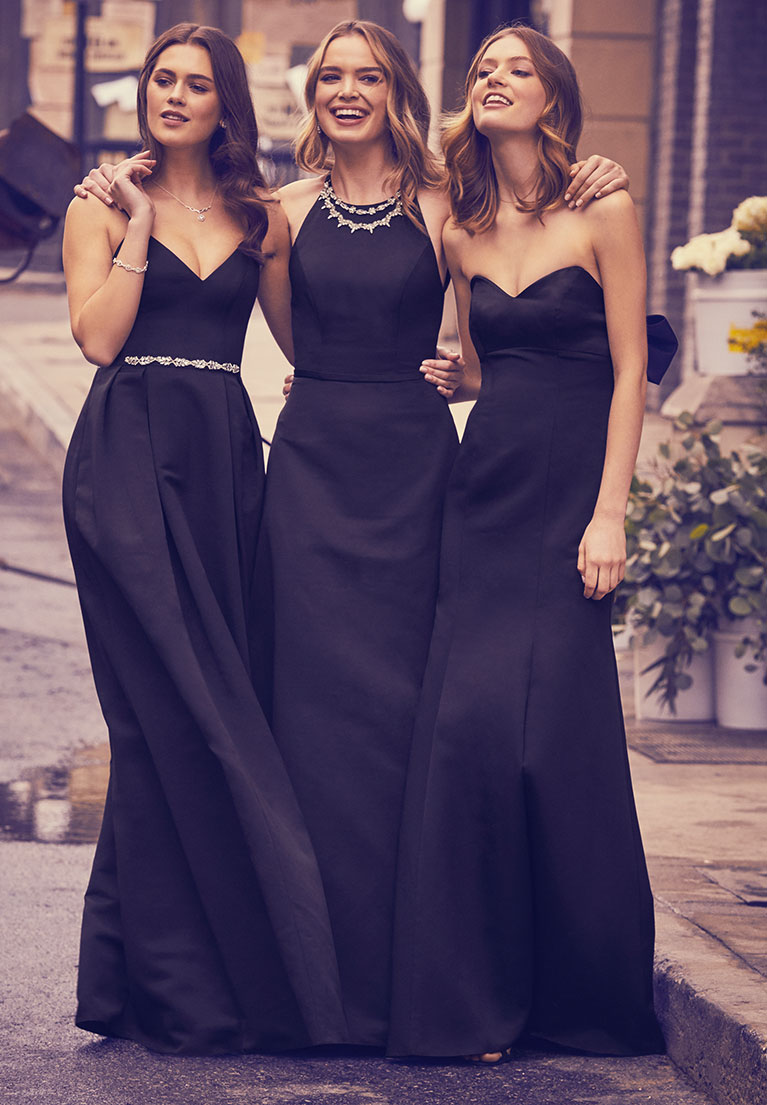 Three bridesmaids wearing black dresses with their arms around each other