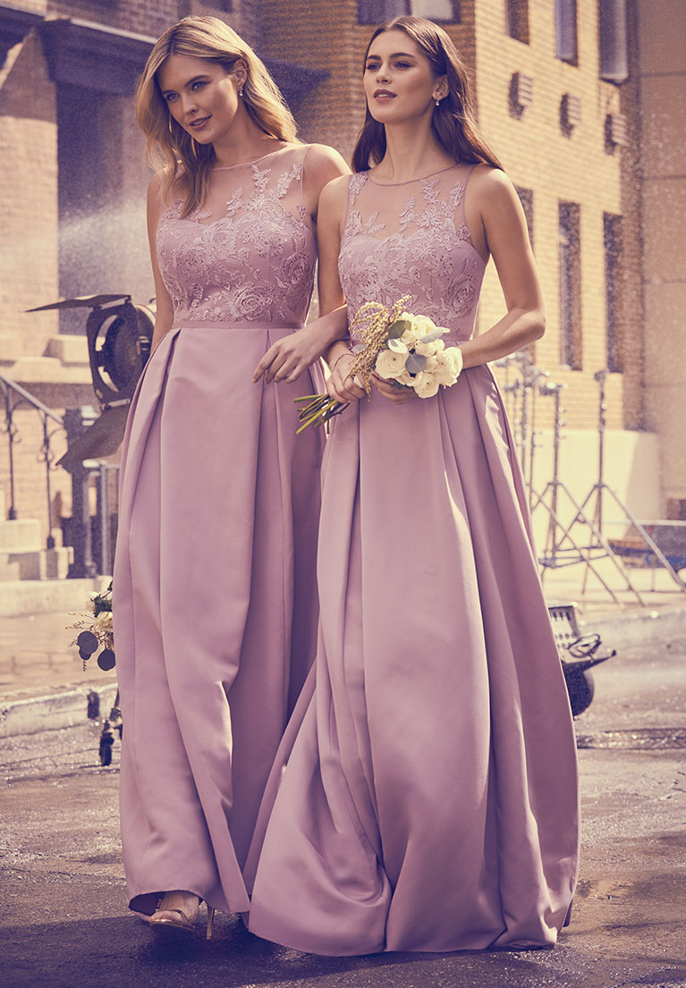Two bridesmaids wearing light purple dresses walking through movie set