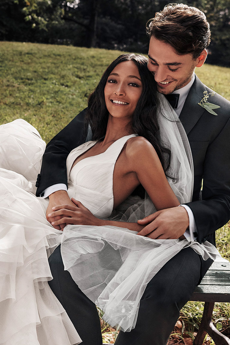 Happy bride in V-neck White by Vera Wang gown and groom in tuxedo on park bench