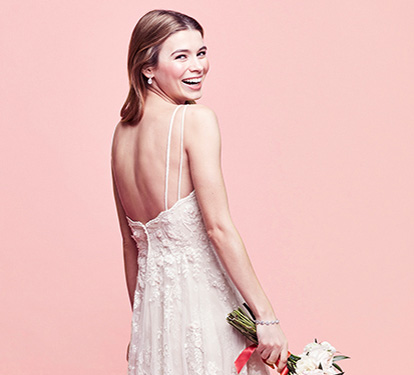 Bride smiling over her right shoulder | Shop wedding dresses