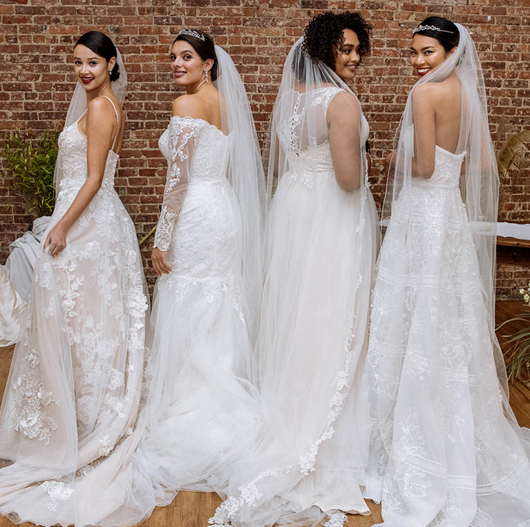 Four model brides posing by brick wall