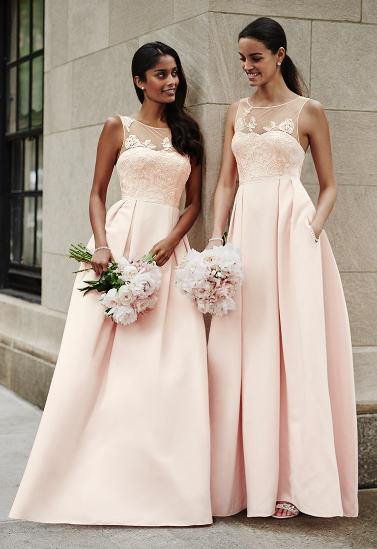 Bridesmaids leaning against NYC building in pink dresses