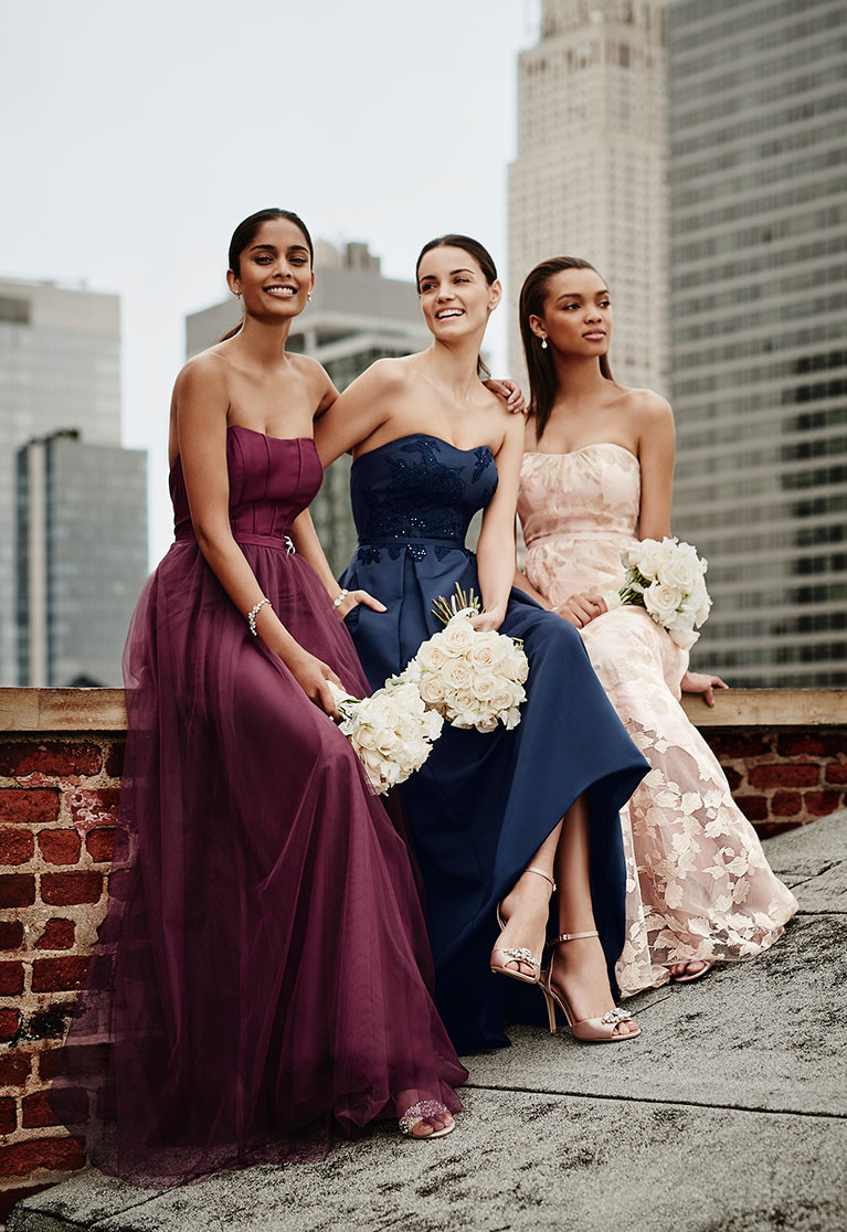 Three Bridesmaids sitting on city rooftop