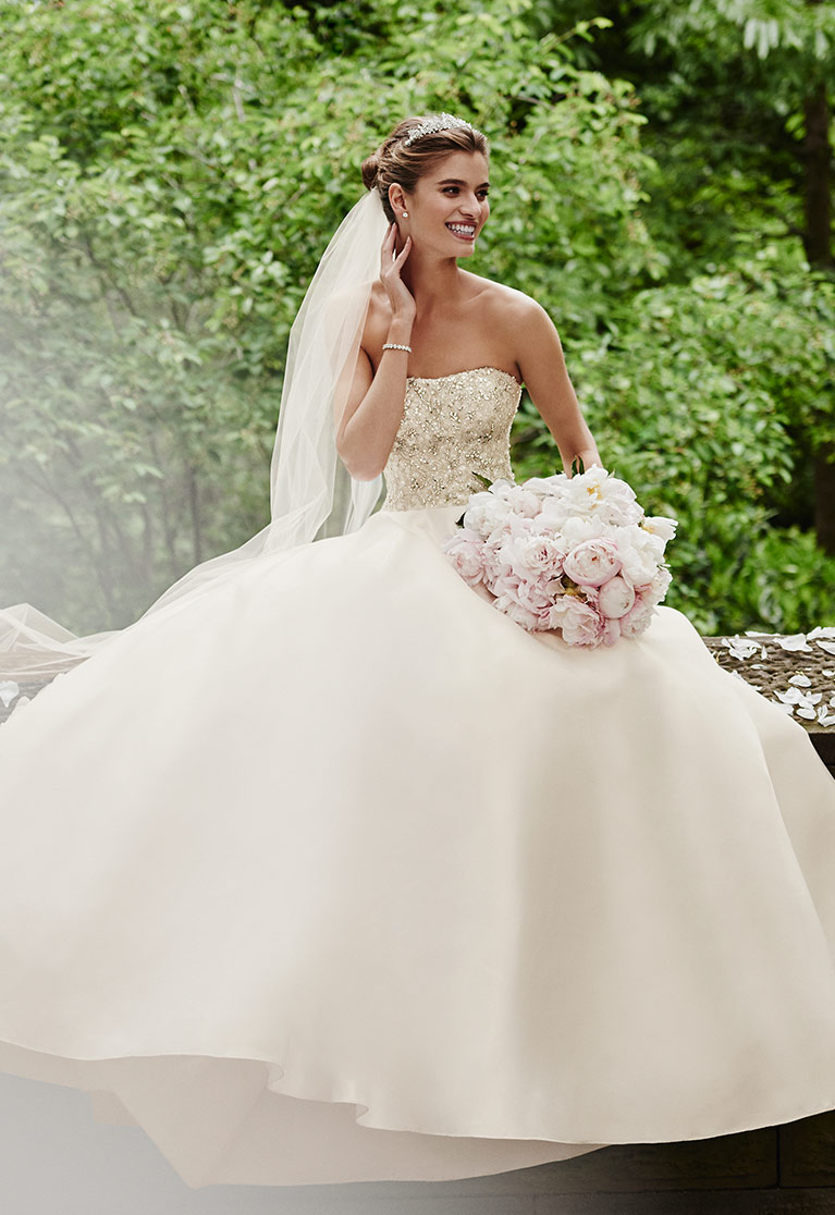 Bride in ball gown with veil and bouquet sitting on park stone wall