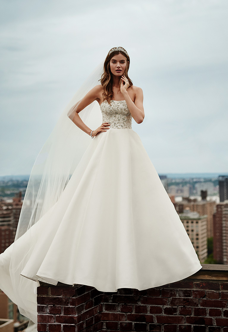 Bride in ball gown standing on the edge of a brick building posing