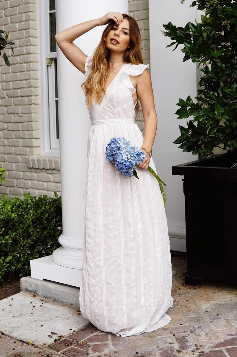 Bride to be in long casual white dress holding blue flowers